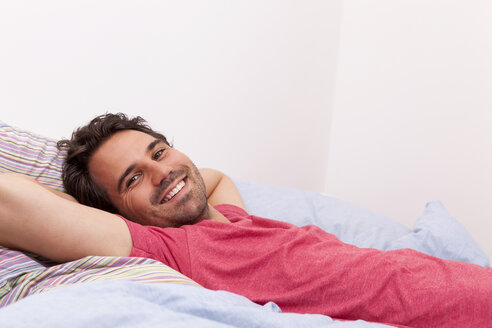 Portrait of smiling young man with hands behind head lying on his bed - JUNF000048