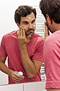 Mirror image of young man applying face cream - JUNF000055
