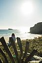 France, Brittany, Camaret-sur-Mer, senior woman sitting at the coast - UUF001778