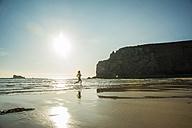France, Brittany, Camaret-sur-Mer, teenage girl running in the ocean - UUF001788