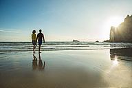 France, Brittany, Camaret-sur-Mer, teenage couple on the beach walking on the beach - UUF001793