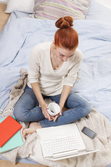 Young woman sitting on her bed with cup of coffee looking at laptop - JUNF000064