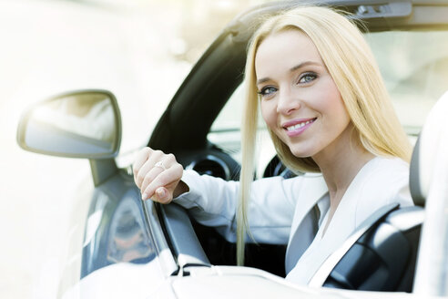 Portrait of smiling young woman sitting in her convertible - GDF000435
