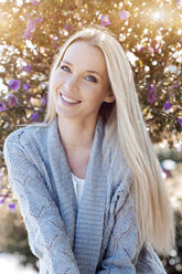 Portrait of smiling young woman wearing light blue cardigan - GDF000440