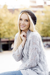 Portrait of smiling young woman wearing wooly hat and cardigan - GDF000443
