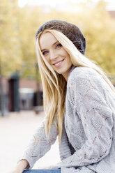 Portrait of smiling young woman wearing wooly hat and cardigan - GDF000444