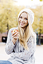 Portrait of smiling young woman holding an apple wearing wooly hat and cardigan - GDF000445