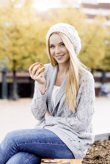 Portrait of smiling young woman holding an apple wearing wooly hat and cardigan - GDF000446