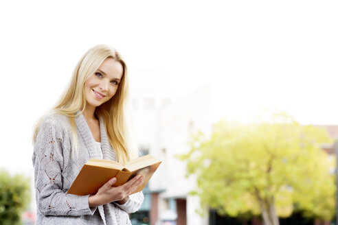 Portrait of smiling young woman with opened book - GDF000455