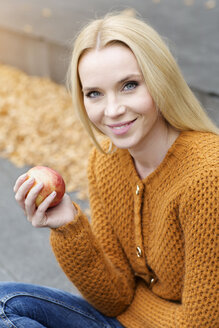 Portrait of smiling young woman holding an apple wearing cardigan - GDF000451