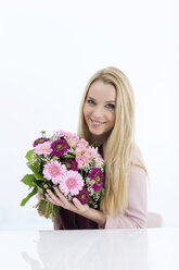 Portrait of smiling young woman holding bunch of flowers - GDF000452