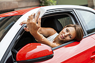 Portrait of smiling young woman sitting in her car taking a selfie with her smartphone - JUNF000072