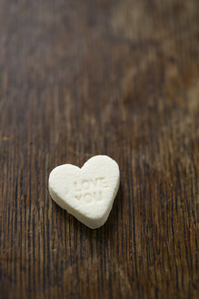 White sugar heart with the words 'Love you' on brown wood - MYF000559