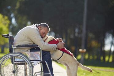 Man in wheelchair hugging dog in park - ZEF000388