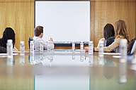 Group of businesspeople looking at empty whiteboard in boardroom - ZEF000266