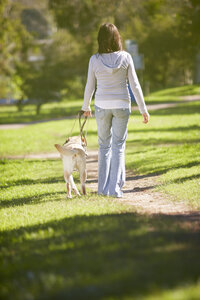 Visually impaired woman walking with guide dog in a park - ZEF000868
