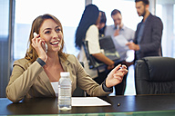 Businesswoman on cell phone in boardroom - ZEF000285
