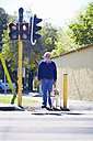 Visually impaired man waiting with his guide dog at pedestrian light - ZEF000997