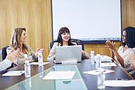 Businesspeople applauding businesswoman in boardroom - ZEF000291