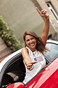 Portrait of happy young woman sitting in a car presenting her driving license - JUNF000080