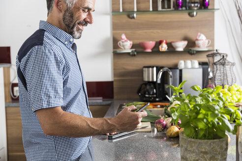 Austria, Man in kitchen using smart phone - MBEF001236