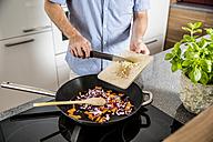 Austria, Man in kitchen putting garlic into pan - MBEF001237