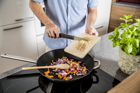 Austria, Man in kitchen putting garlic into pan - MBEF001237