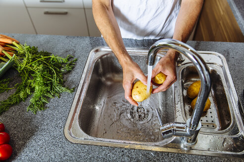 Austria, Man in kitchen washing vegetables - MBEF001251