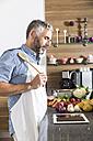 Austria, Man in kitchen with digital tablet preparing food - MBEF001263