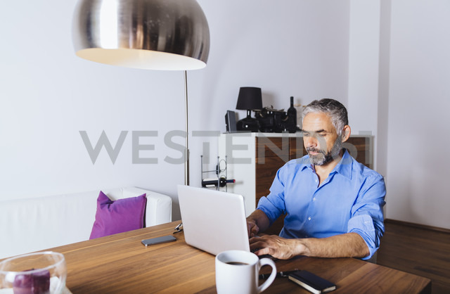 Businessman working with laptop at home office - MBEF001286