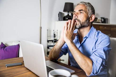 Portrait of pansive businessman working with laptop at home office - MBEF001287