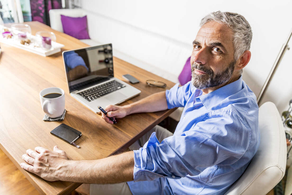 Portrait of businessman with laptop at his home office - MBEF001288 - Martin Benik/Westend61