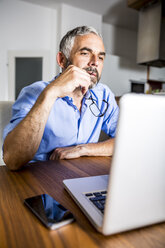 Pensive businessman working with laptop at home office - MBEF001289