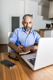 Portrait of businessman making notes at home office - MBEF001293
