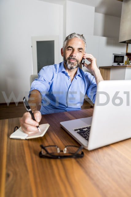 Portrait of businessman telephoning with his smartphone while making notes - MBEF001294 - Martin Benik/Westend61