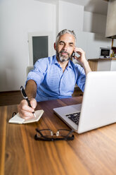Portrait of businessman telephoning with his smartphone while making notes - MBEF001294