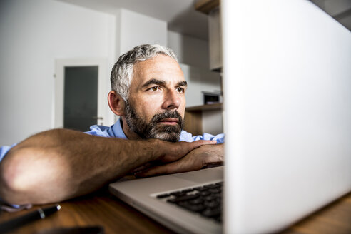 Portrait of man staring at his laptop - MBEF001296