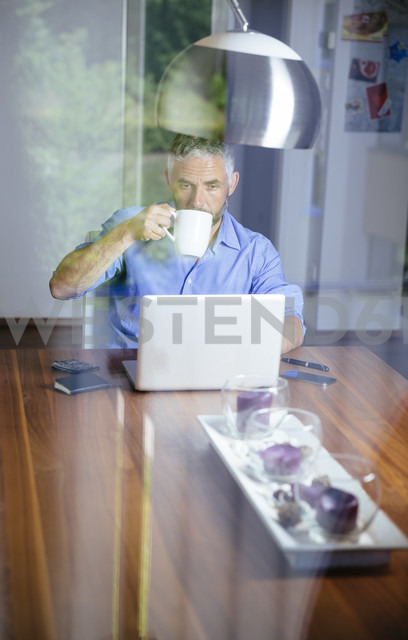 Businessman working with laptop at home office drinking coffee - MBEF001185