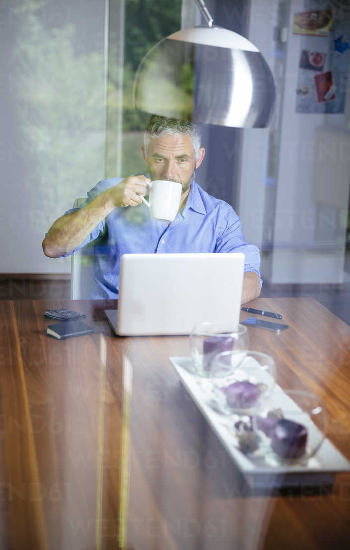 Businessman working with laptop at home office drinking coffee - MBEF001185 - Martin Benik/Westend61
