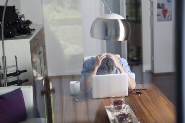 Overstressed businessman with head in his hands sitting at his home office - MBEF001300