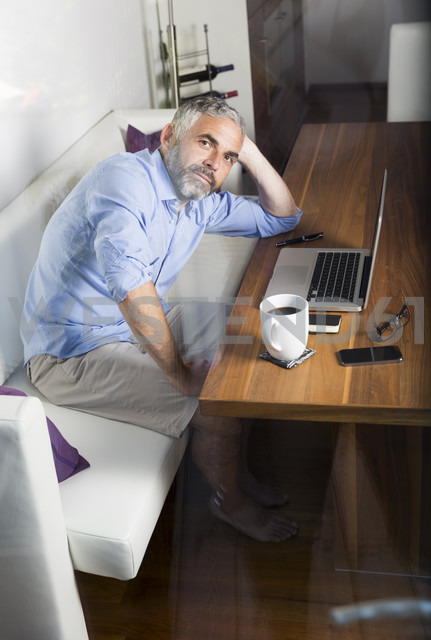 Portrait of businessman with laptop at his home office - MBEF001302