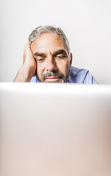 Portrait of boring businessman with laptop at home office - MBEF001188
