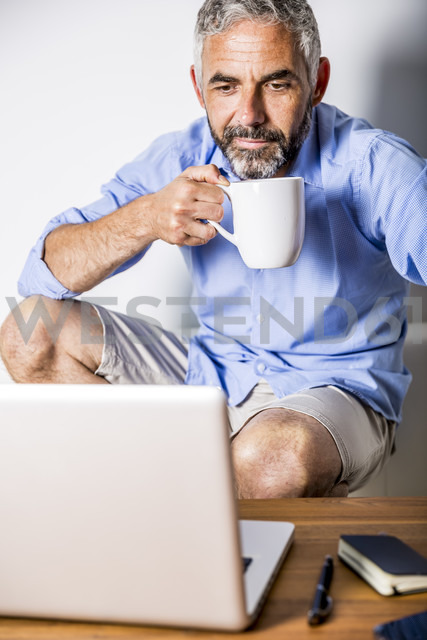 Potrait of businessman having a coffee break at his home office - MBEF001189