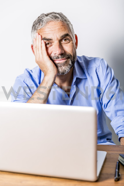 Potrait of smiling businessman with laptop at his home office - MBEF001190