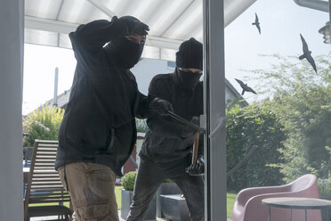 Two burglars opening terrace door of an one-family house with hammer and crowbar at daytime - ONF000619