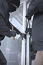 Two burglars opening terrace door of an one-family house with hammer and crowbar at daytime, partial view - ONF000621