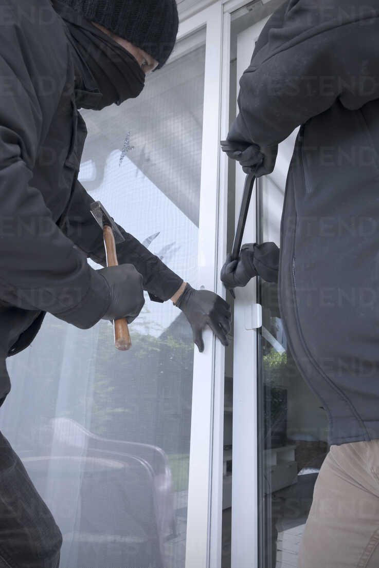 Two burglars opening terrace door of an one-family house with hammer and crowbar at daytime, partial view - ONF000621 - noonland/Westend61
