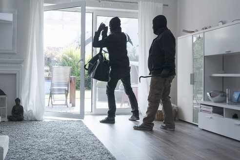 Two burglars leaving an one-family house with their loot at daytime - ONF000628