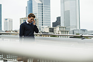 Germany, Hesse, Frankfurt, young businessman walking on a bridge telephoning with his smartphone - UUF001820