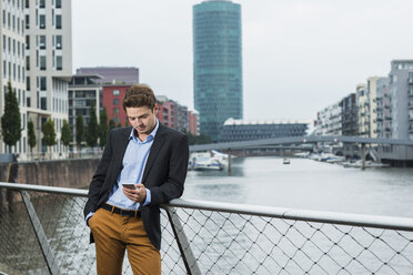 Germany, Hesse, Frankfurt, young businessman standing on a bridge using his smartphone - UUF001830